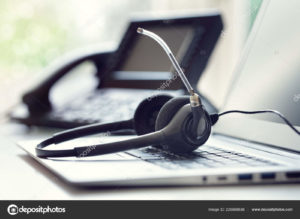 A headset rests on top of a laptop keyboard.