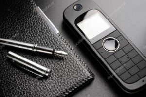 A cellphone sits near a padfolio with a pen next to it.