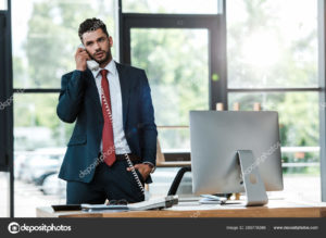 A man in a suit uses a telephone in the office.