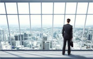 A business man overlooks a city from an office view.