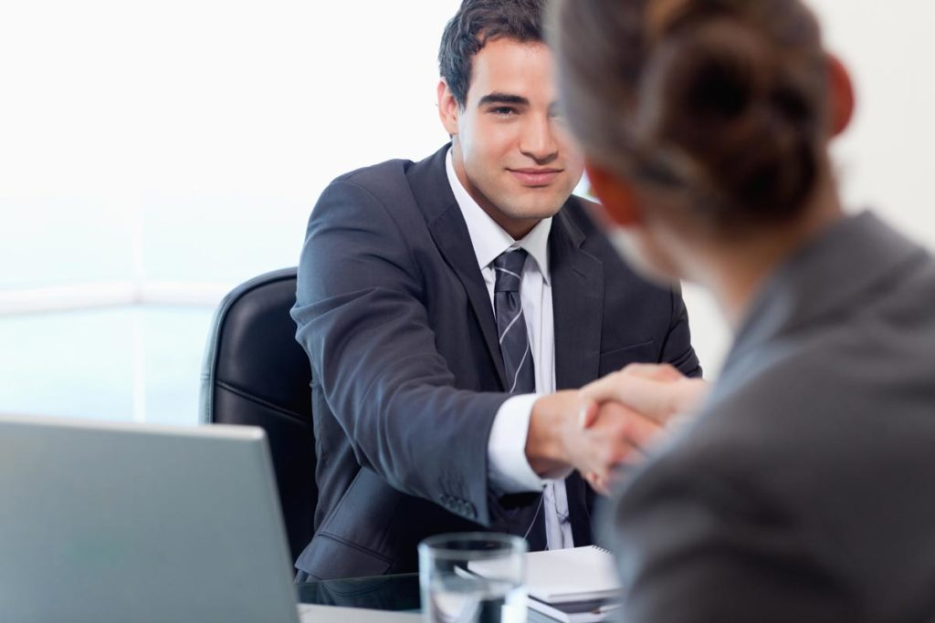 A man in a suit shakes the hand of a woman in a business meeting.