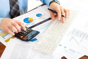 An accountant in a blue shirt types numbers into a calculator and keyboard.