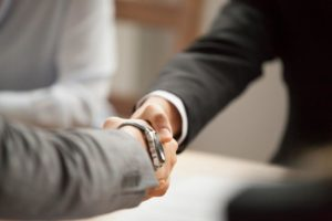 Two accountants in suits shake hands after making a deal.