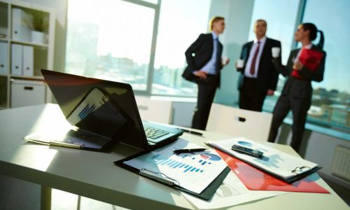 A group of 3 accountants discuss business in an office.